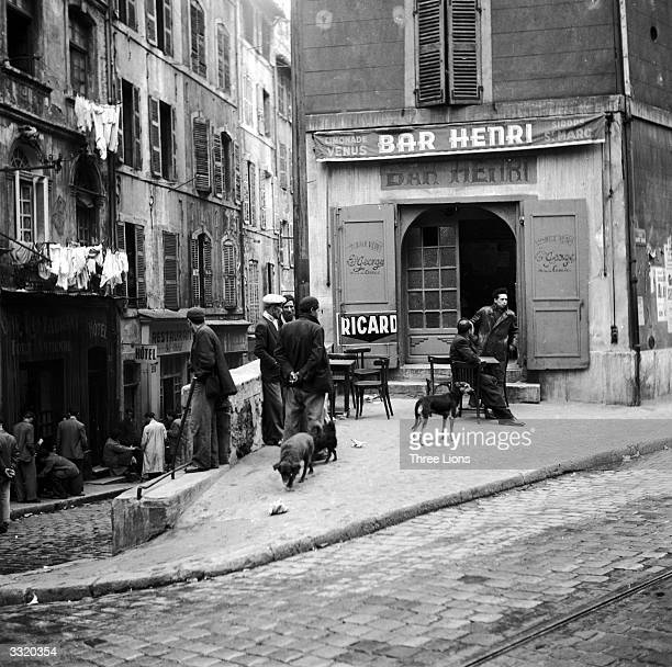 In the old quarter of Marseilles men loiter outside a dilipated bar