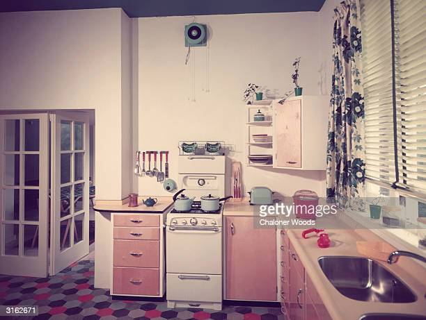 Interior of a fifties fitted kitchen with a linoleum tiled floor and venetian blinds