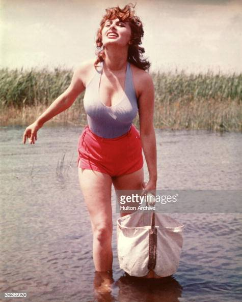 Italian actor Sophia Loren wearing lowcut lavender tank top and red hot shorts carries a canvas bag while crossing a stream