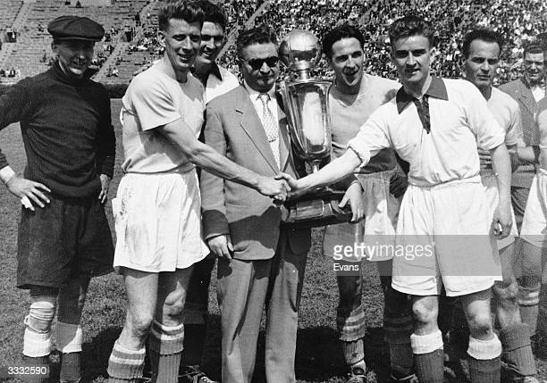 Jack Flamhaft President of the American Soccer League holds the Lewis Cup before the final Players from the teams competing for the trophy stand...