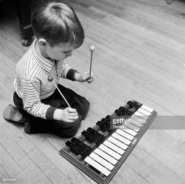 Little Michael Owen bangs away at a xylophone during a lesson at a musical kindergarten school