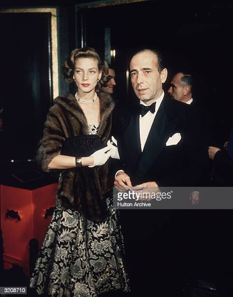 Married American actors Lauren Bacall and Humphrey Bogart stand in a foyer after arriving together Bacall wears a brocade dress a mink wrap and a...