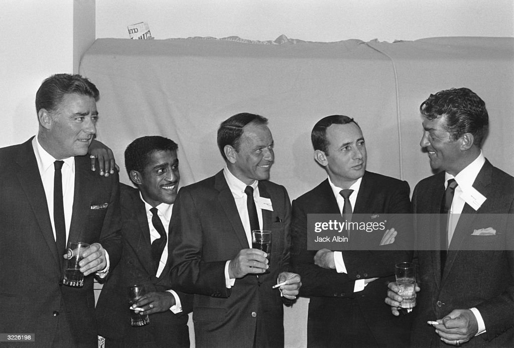 British actor Peter Lawford (1923 - 1984), American actor, singer, and dancer Sammy Davis Jr. (1925 - 1990), actor and singer Frank Sinatra (1915 - 1998), actor Joey Bishop, and actor and singer Dean Martin (1917 - 1995). All are wearing dark suits, and all but Bishop are holding drinks.