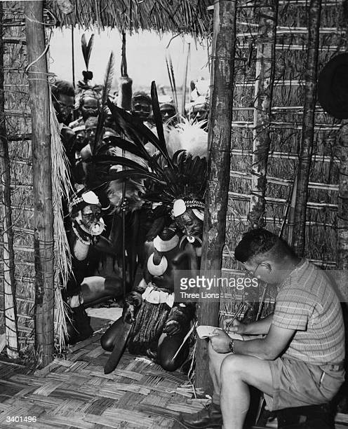 Natives of New Guinea cautiously regard an Australian journalist as he writes his story from inside a hut