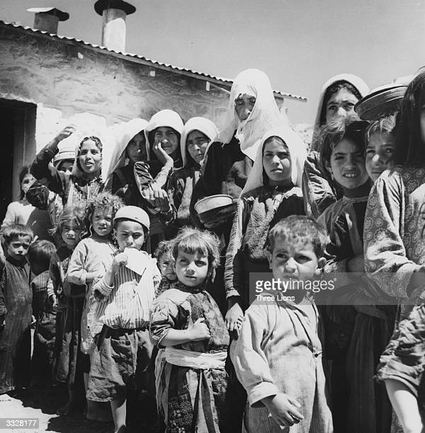 Palestinian refugees from Israel form a queue by the food tent in their camp in Amman