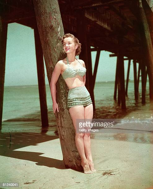 Circa 1955 Portrait of American actor and singer Debbie Reynolds wearing a twopiece swimsuit while leaning against a wooden pier post on a beach 1950s