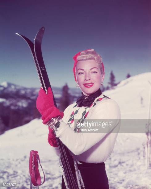 Portrait of American actor Lana Turner wearing a skiing outfit consisting of a turban gloves a knit sweater and ski pants holding skis on a snowy ski...