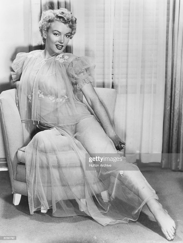 Portrait of American actor Marilyn Monroe wearing a sheer nightgown while posing on a chair mid1950s