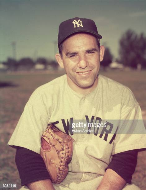 Portrait of American baseball player Yogi Berra in his New York Yankees uniform with a baseball glove under his arm New York City
