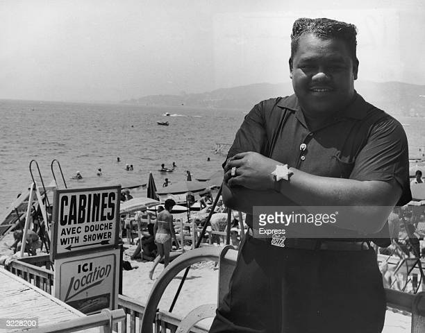 Portrait of American rock n' roll singer and pianist Fats Domino posing at the beach with people relaxing and swimming behind him France He wears a...