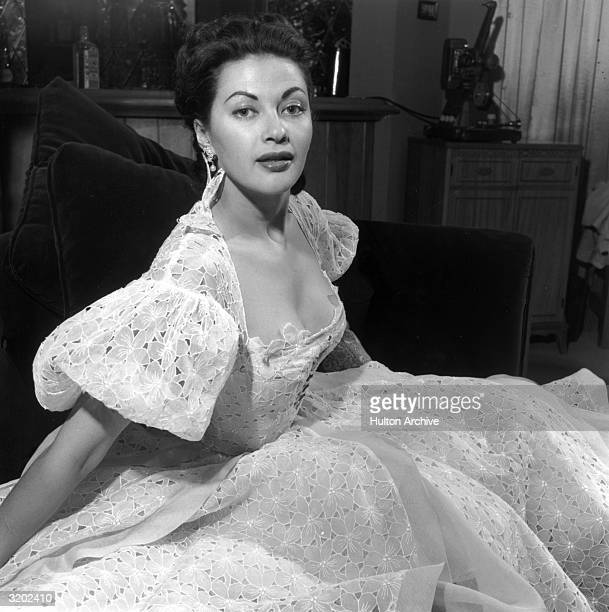 Portrait of Canadian actor Yvonne De Carlo seated in a lowcut eyelet dress with a full skirt and puffed sleeves