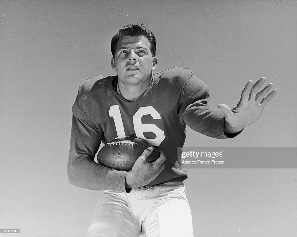 Portrait of New York Giants football player <a gi-track='captionPersonalityLinkClicked' href=/galleries/search?phrase=Frank+Gifford&family=editorial&specificpeople=214258 ng-click='$event.stopPropagation()'>Frank Gifford</a>, wearing his jersey (#16), holding a football outdoors.
