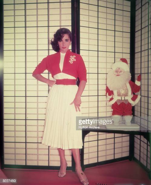 Promotional portrait of Britishborn actor Elizabeth Taylor standing next to a Santa Claus doll in front of a shoji screen Taylor wears a red bolero...