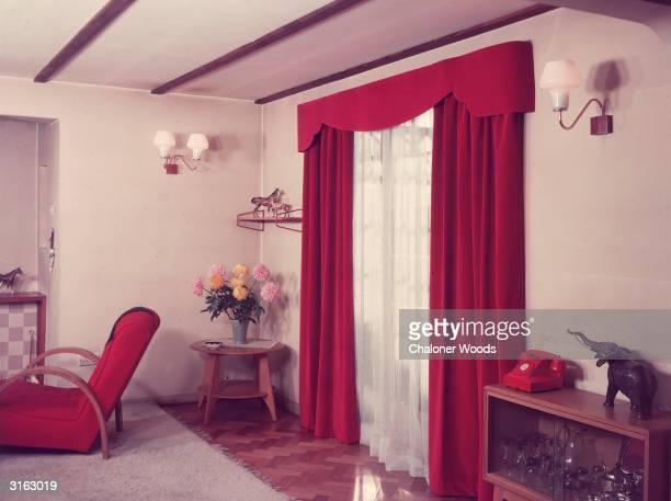 Red velour curtains cover French windows in a fifties living room with a parquet floor