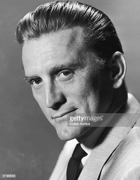 Semiprofile closeup portrait of American actor Kirk Douglas wearing a suit and smiling
