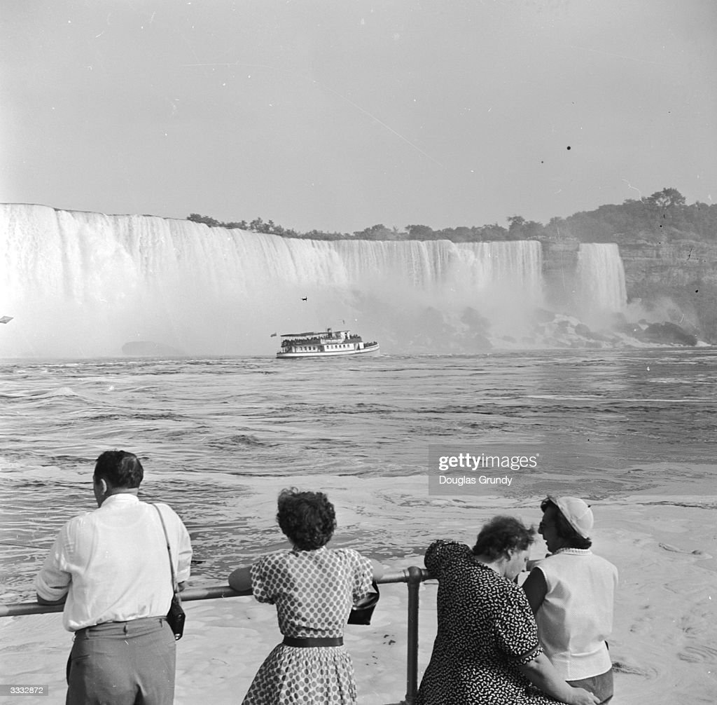 Sightseers watch a pleasure boat at Niagara Falls on the Niagara River east central North America The Falls can be viewed from both the Canadian and...