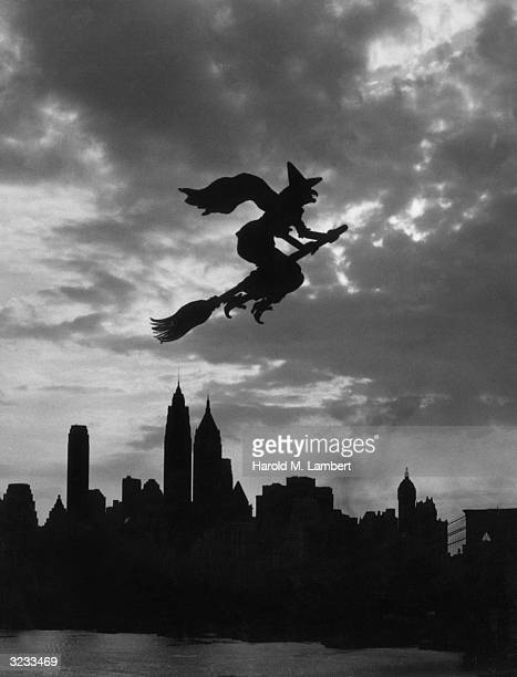 Silhouette of a witch on a broomstick flying over the skyline of New York City Halloween