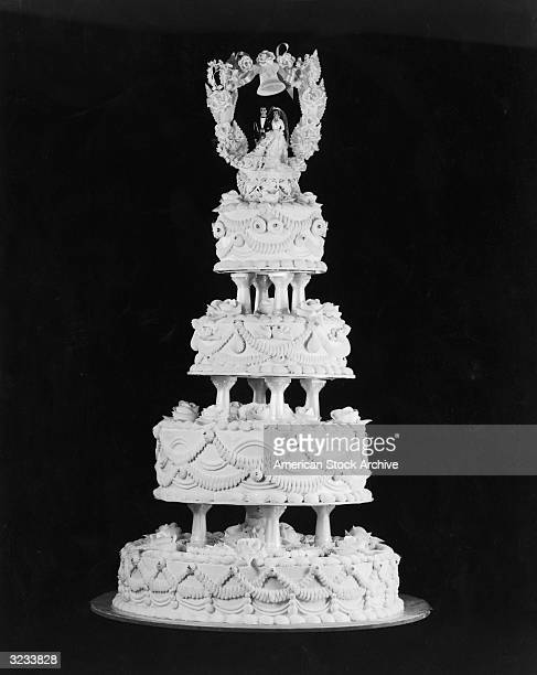 Still life of a fourtiered wedding cake with Bride and Groom figurines on the top tier under a wedding bell