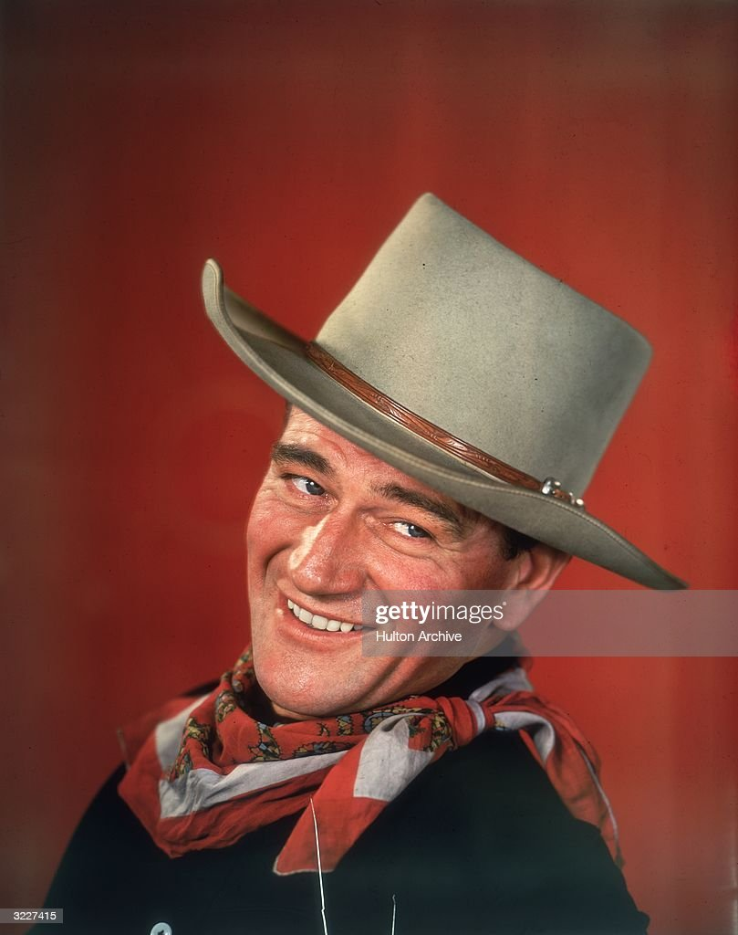 Studio headshot portrait of American actor <a gi-track='captionPersonalityLinkClicked' href=/galleries/search?phrase=John+Wayne&family=editorial&specificpeople=69997 ng-click='$event.stopPropagation()'>John Wayne</a> smiling in front of a red background, dressed in Western garb, with his head turned to the side.