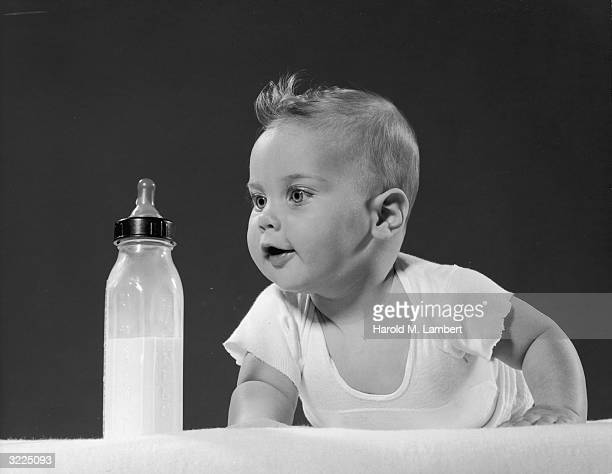 Studio image of a baby crawling with an excited expression toward a bottle with milk in it There is a gray backdrop