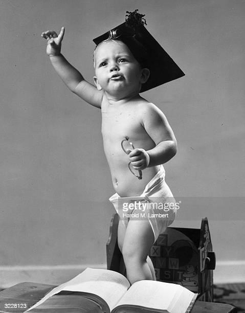Studio image of a male infant standing with his finger raised wearing a graduation cap and holding a pair of eyeglasses