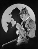 Studio portrait of a man dressed as British detective Sherlock Holmes with a plaid cap a meerschaum pipe and a magnifying glass His silhouette is...