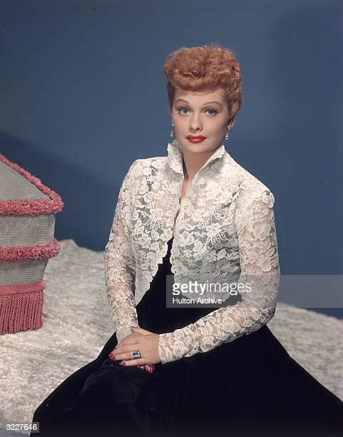 Studio portrait of American actor and comedian Lucille Ball wearing a white lace bolero jacket over a black gown