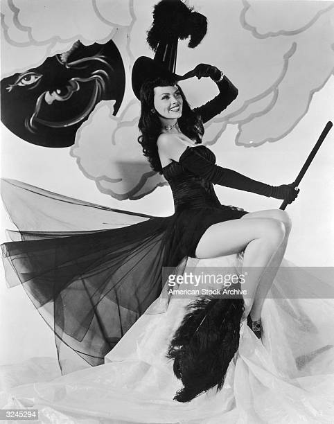 Studio portrait of American actor Dusty Anderson posing in a witch's hat and a strapless chiffon costume while holding a feathered broom