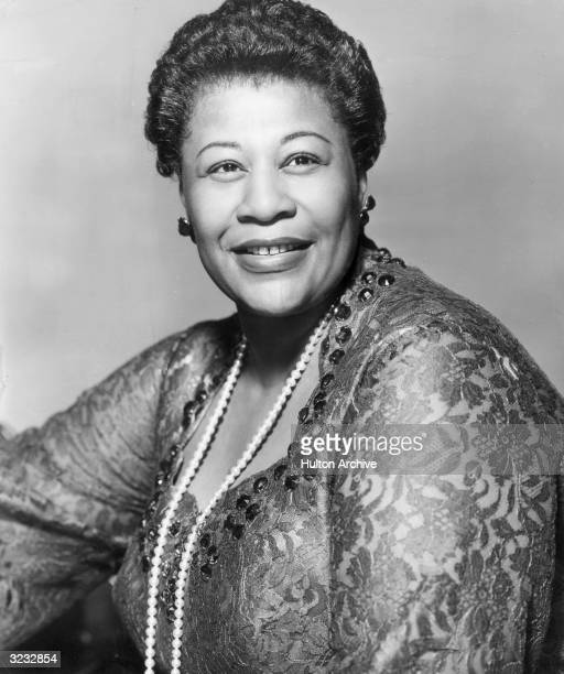 Studio portrait of American jazz singer Ella Fitzgerald wearing a lace dress and pearls 1950s