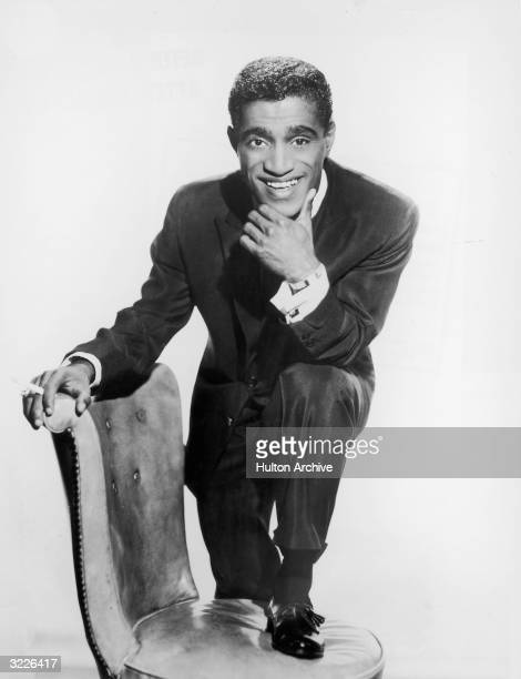 Studio portrait of American singer and actor Sammy Davis Jr with one leg up on a chair