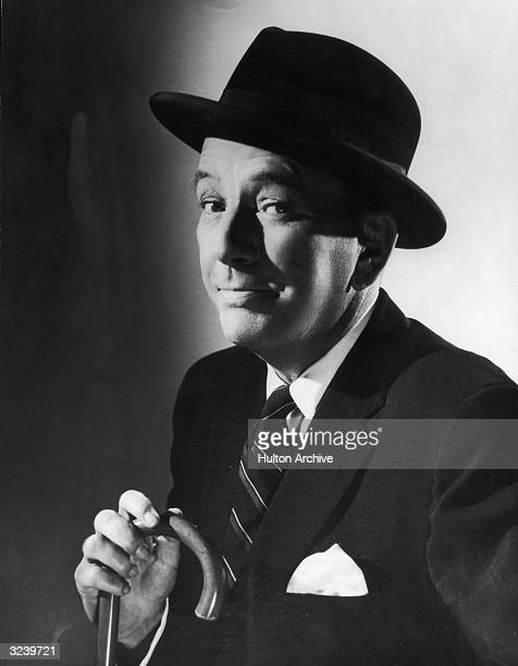 Studio portrait of British actor and playwright Noel Coward wearing a hat and holding a cane Geneva Switzerland