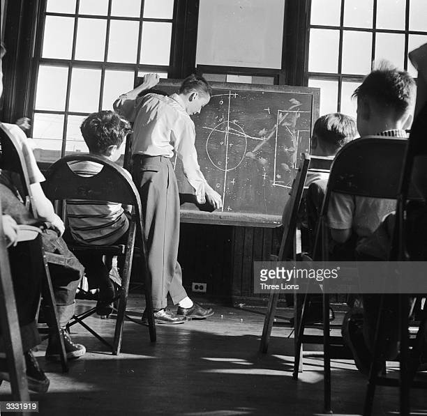 The captain of the school football team using a blackboard to explain tactics to members of his team in a classroom