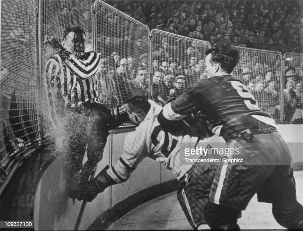 DETROIT circa 1955 The Detroit Red Wings' star Gordie Howe number 9 checks a Chicago Black Hawk opponent into the boards during a National Hockey...