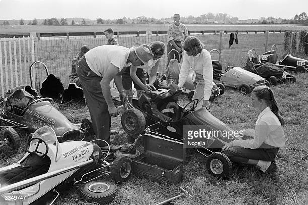 The whole family lends a hand with the repairs and fine tuning of the miniature racer at a junior motor race