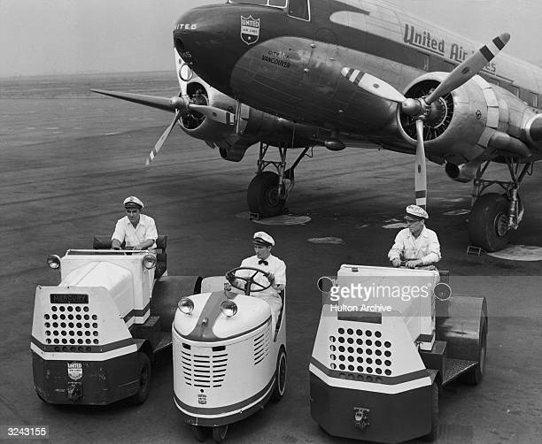 Three airport cart drivers wait on a tarmac with a United Airlines propeller plane in the background
