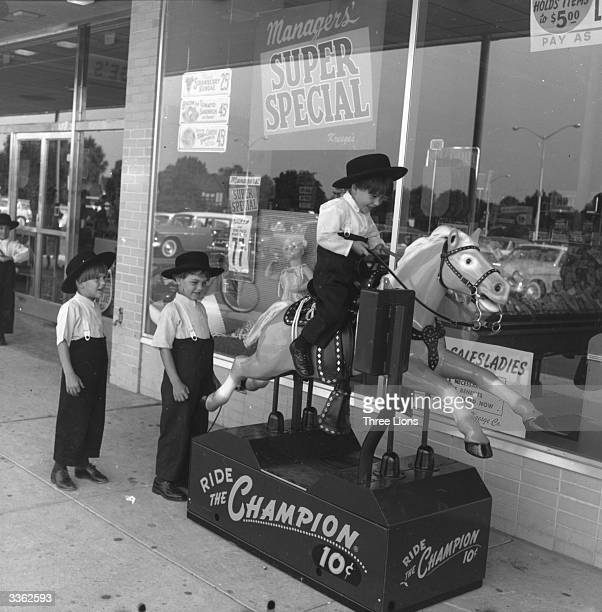 Three little Amish boys take it in turns to have a go on the 'Champion' ride outside the grocery store USA