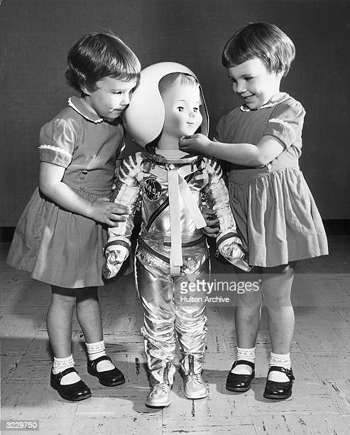 Threeandahalf year old twins Maureen and Leigh Soden play with a 3 foot high toy astronaut doll at the American Rocket Society scientific exhibit...