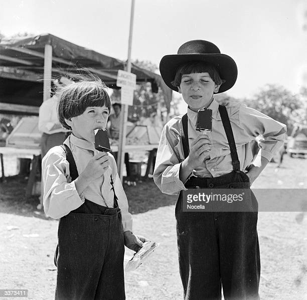 Two Amish boys wearing traditionally plain clothing enjoying ice cream at a local country fair