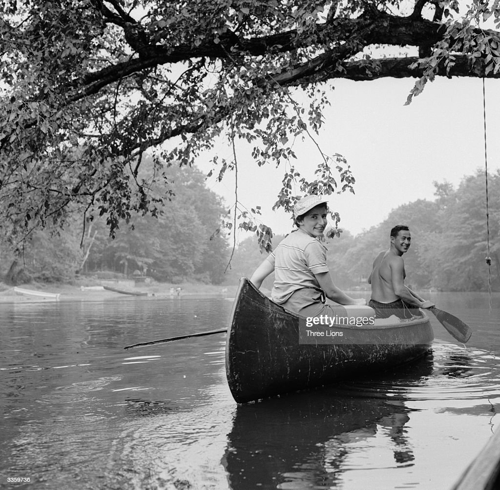 Two canoeists paddling down the Passaic River, New Jersey.