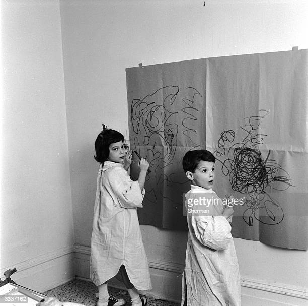 Two children dawing on a piece of brown paper taped onto a wall