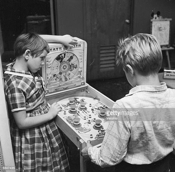 Two children playing a mini pinball machine