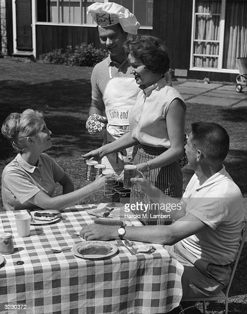 Two couples have a backyard barbecue A woman serves glasses of beer to her guests in a metal holder while her husband stands behind her wearing a...