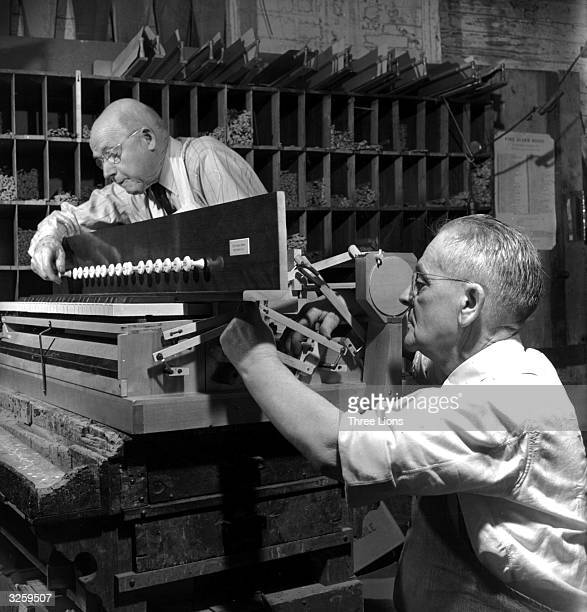 Two craftsmen from Brattleboro Vermont adjusting the various stops on a newly constructed harmonium church organ