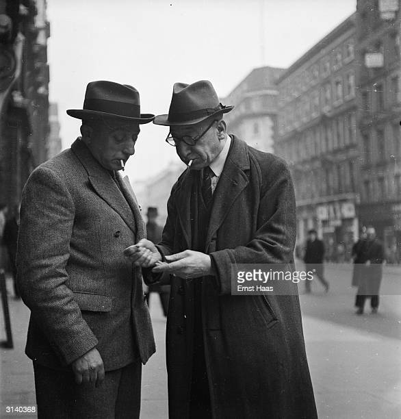 Two elderly man cigarettes clamped between their lips stand on a London street checking their change