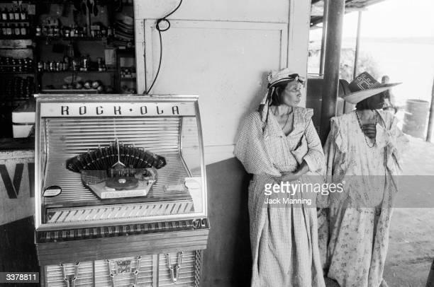 Two indegenous Guajira women waiting on a street corner next to a juke box in Maracaibo Venezuela