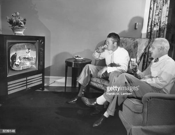 Two men drink glasses of beer while watching a baseball game on television in a living room