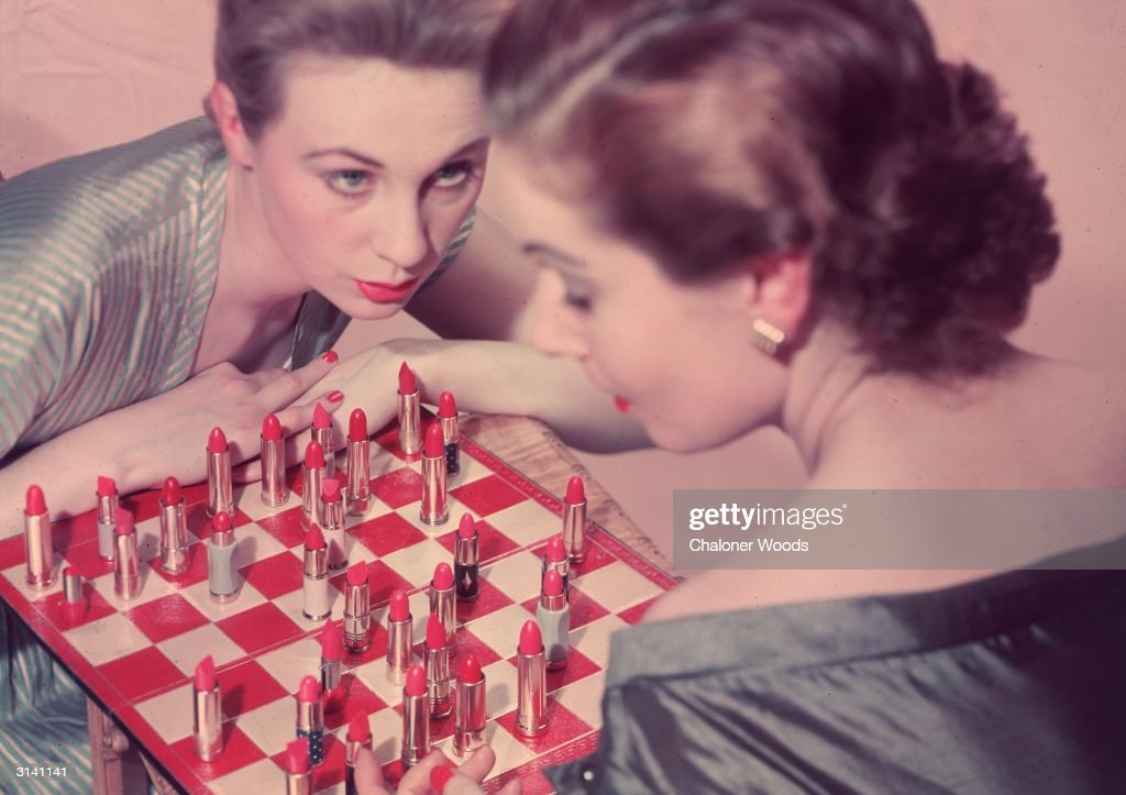 Two women playing an unusual game of chess, with lipstick instead of chess pieces.