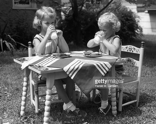 Two young girls sit at a table outdoors drinking glasses of milk to go with their plates of snacks