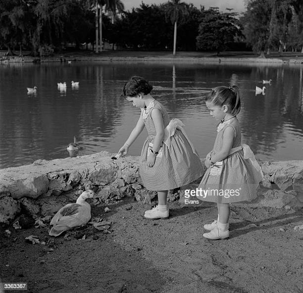 Two young sisters Maria and Conchita Gondar feeding ducks at the park lake in Marianao Cuba