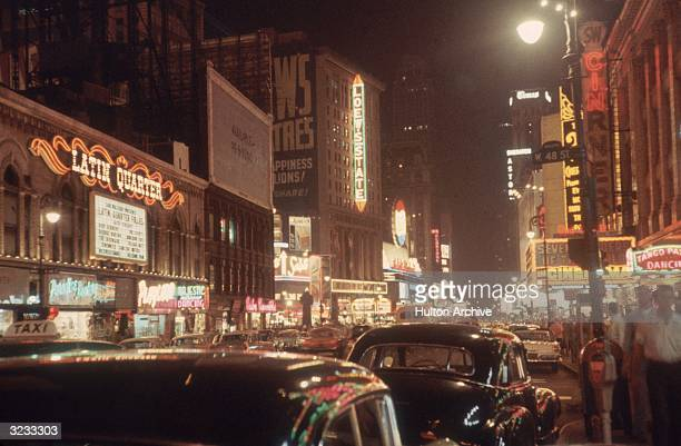 View of neon signs lit up at night in Times Square facing south on Seventh Avenue from West 48th Street New York City
